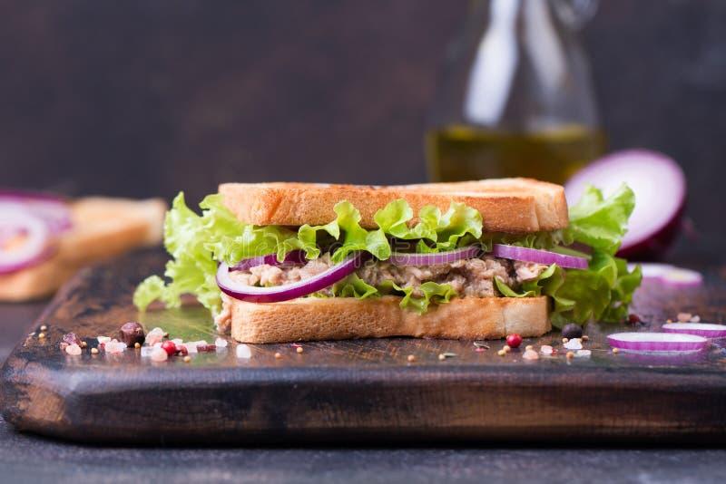 Sanduíche dos peixes de atum com cebola, alface e azeite em uma placa de madeira fotos de stock royalty free