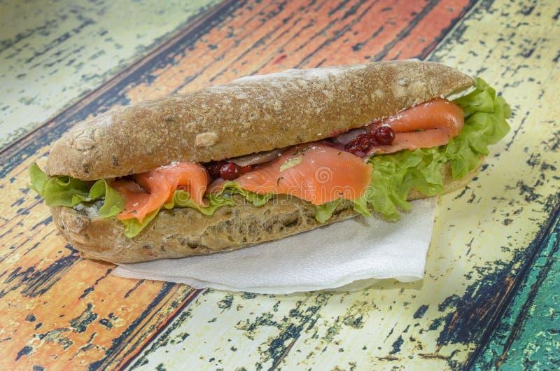Sanduíche dos salmões com verdes em um bolo delicioso fotografia de stock royalty free