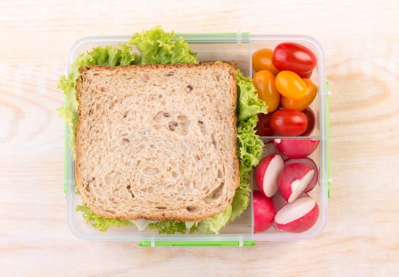 Sanduíche em uma cesta de comida com tomates e rabanete fotos de stock