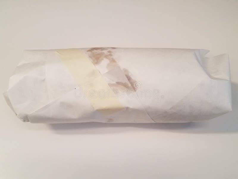 Sanduíche envolvido no papel com a fita na superfície branca fotografia de stock royalty free