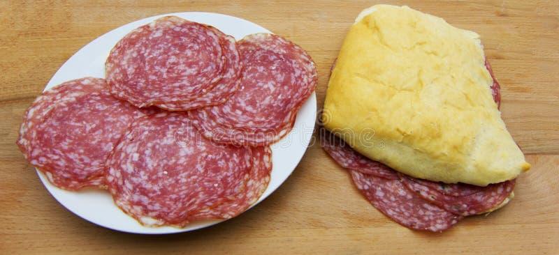 Sanduíche feito fresco do salame, com fatias de salame em um prato branco cerâmico, no fundo de madeira imagem de stock royalty free