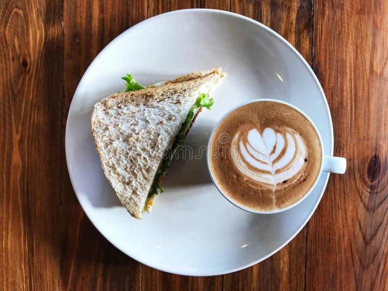 Sanduíche fresco e de arte do Latte copo de café no prato branco foto de stock