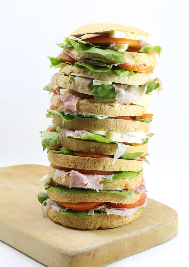 Sanduíche grande com o tomate do presunto do queijo em uma placa e em um branco de corte imagem de stock royalty free