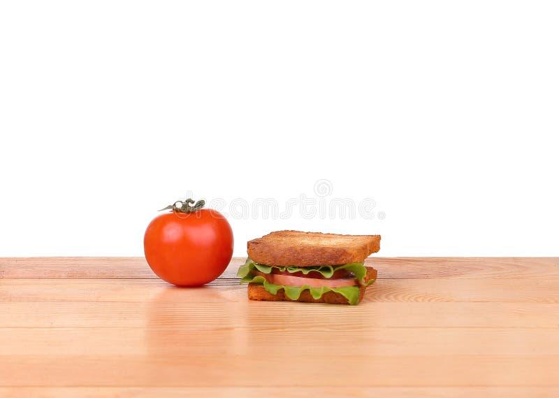 Sanduíche grande com os legumes frescos na placa de madeira no fundo branco fotos de stock royalty free