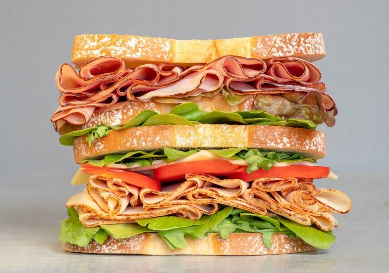 Sanduíche grande da carne do supermercado fino enchido com queijo, presunto, tomate Sandu?che de clube Vista acima isolada no fun imagem de stock royalty free