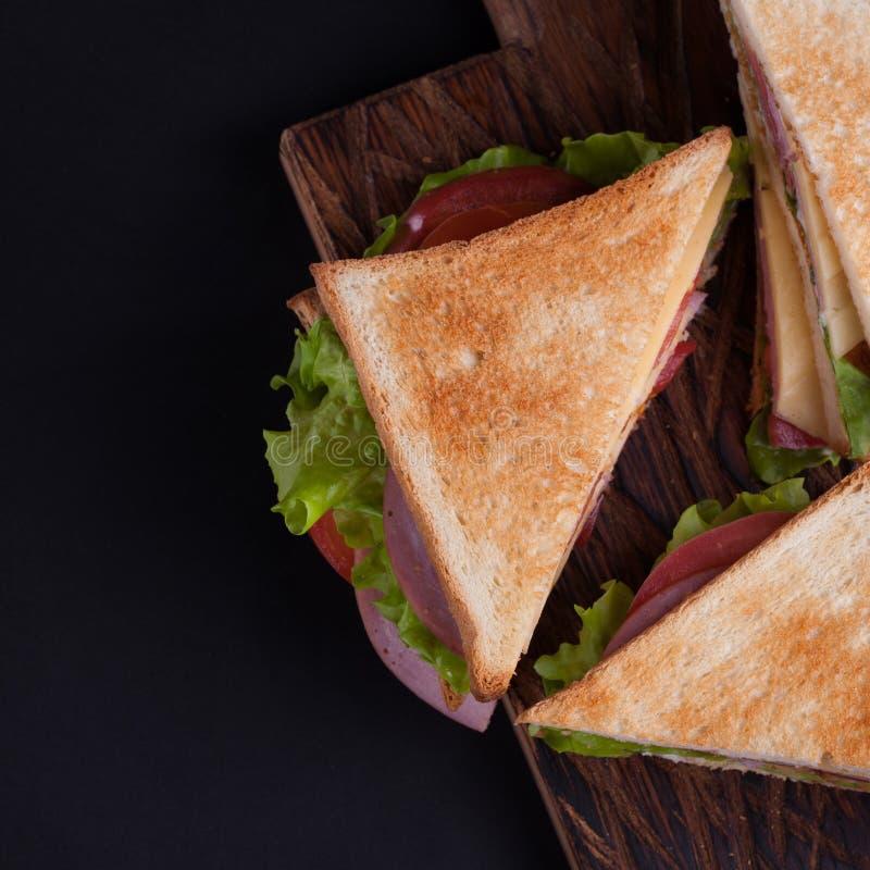 Sanduíche grande do close-up com presunto, queijo, tomates e salada no pão brindado em um fundo escuro Vista superior com espaço  foto de stock royalty free