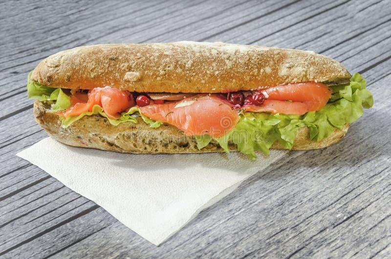 Sanduíche grande e entusiasta com peixes vermelhos, faixa dos salmões, salada, arando e o bolo fresco o conceito do almoço em um  foto de stock royalty free