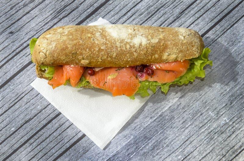 Sanduíche grande e entusiasta com peixes vermelhos, faixa dos salmões, salada, arando e o bolo fresco o conceito do almoço em um  imagem de stock