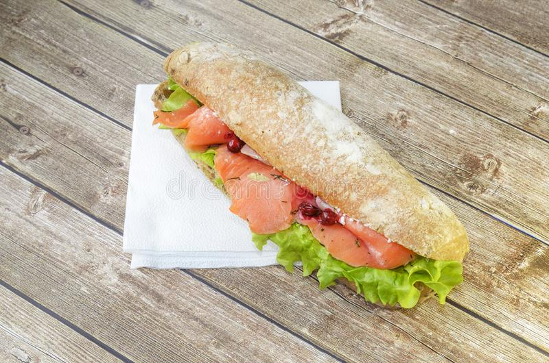 Sanduíche grande e entusiasta com peixes vermelhos, faixa dos salmões, salada, arando e o bolo fresco o conceito do almoço em uma imagens de stock