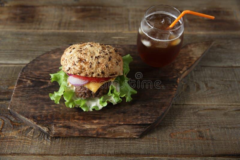 Sanduíche grande - Hamburger com carne, tomates, cebolas, queijo, alface e um bolo do sésamo em um fundo de madeira foto de stock