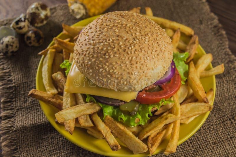 Sanduíche grande - hamburguer do Hamburger com carne, queijo, tomate Em um fundo rústico de madeira Close-up foto de stock royalty free