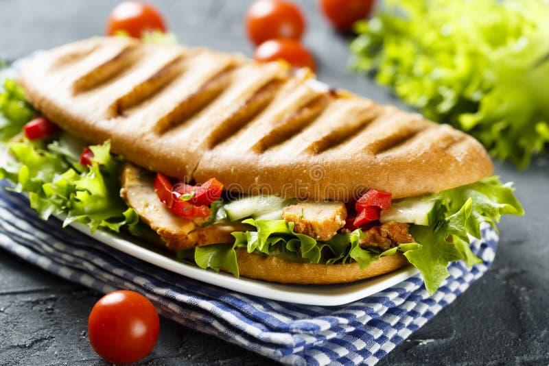 Sanduíche grelhado com galinha, salada verde e vegetais imagem de stock