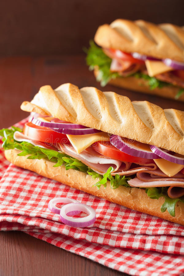 Sanduíche longo do baguette com o tomate e a alface do queijo do presunto foto de stock royalty free