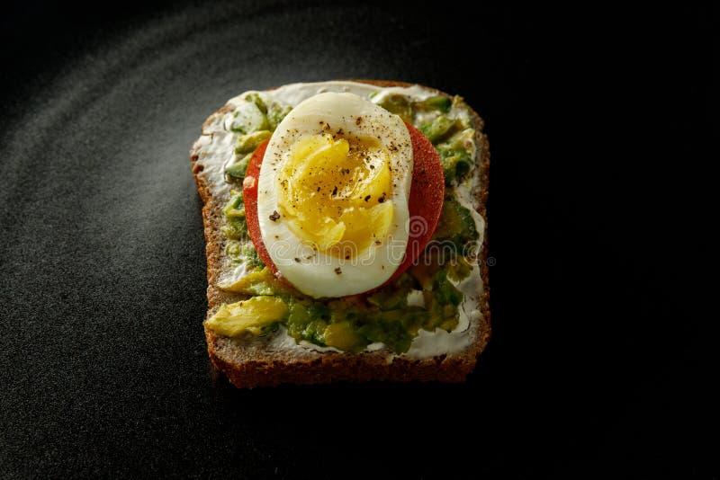Sanduíche no fundo preto pão, ovo, tomate, abacate imagem de stock