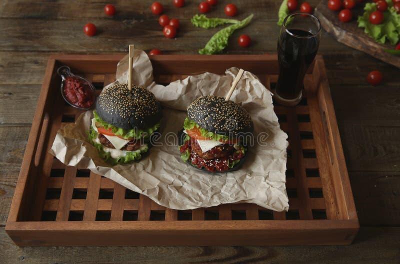 Sanduíche preto, hambúrguer ou hambúrguer com carne de bovino ou de frango, tomates, queijo, alface e um pão de sésamo num papel  foto de stock royalty free