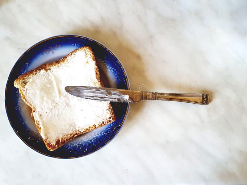Sanduíche quadrado em uma placa com uma beira azul e uma faca Fundo branco com divórcios cinzentos fotografia de stock