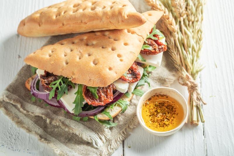 Sanduíche saboroso com rúcula, os tomates secados e o queijo imagem de stock royalty free