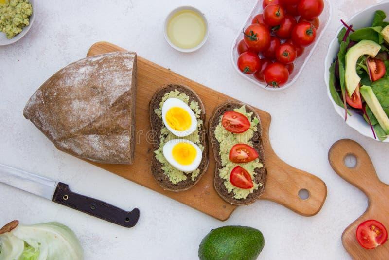 Sanduíche saboroso do vegetariano com abacate, ovo, tomate e na placa de madeira Almo?o delicioso saud?vel imagem de stock royalty free