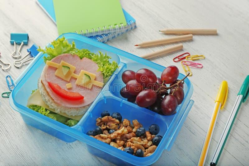 Sanduíche saboroso e frutos na cesta de comida e nos artigos de papelaria fotografia de stock