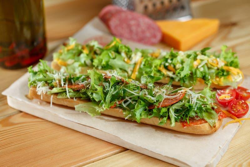 Sanduíche submarino do baguette duro fresco saudável com salame, queijo e rucola Foco seletivo fotos de stock royalty free