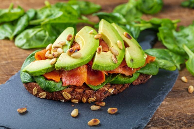 Sanduíche wholegrain do pão dos salmões e do abacate com espinafres foto de stock royalty free