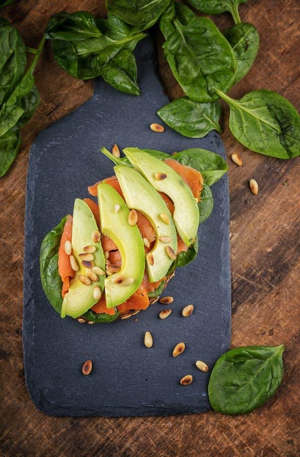 Sanduíche wholegrain do pão dos salmões e do abacate com espinafres, v superior fotos de stock royalty free