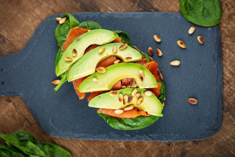 Sanduíche wholegrain do pão dos salmões e do abacate com opinião superior dos espinafres imagens de stock royalty free
