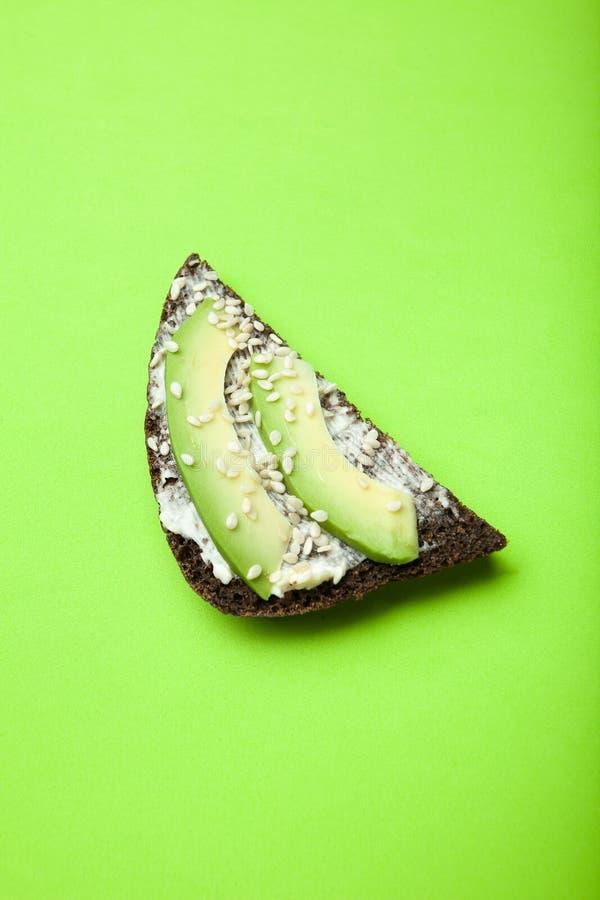 Sanduíches úteis com abacate, queijo, sésamo e pão preto em um fundo verde-claro, verticalmente fotos de stock