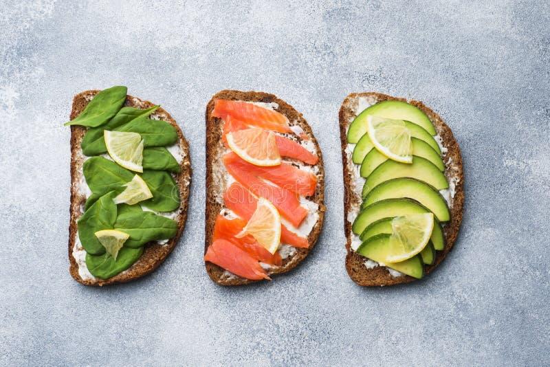 Sanduíches abertos com os salmões dos espinafres e do abacate em uma tabela cinzenta foto de stock royalty free