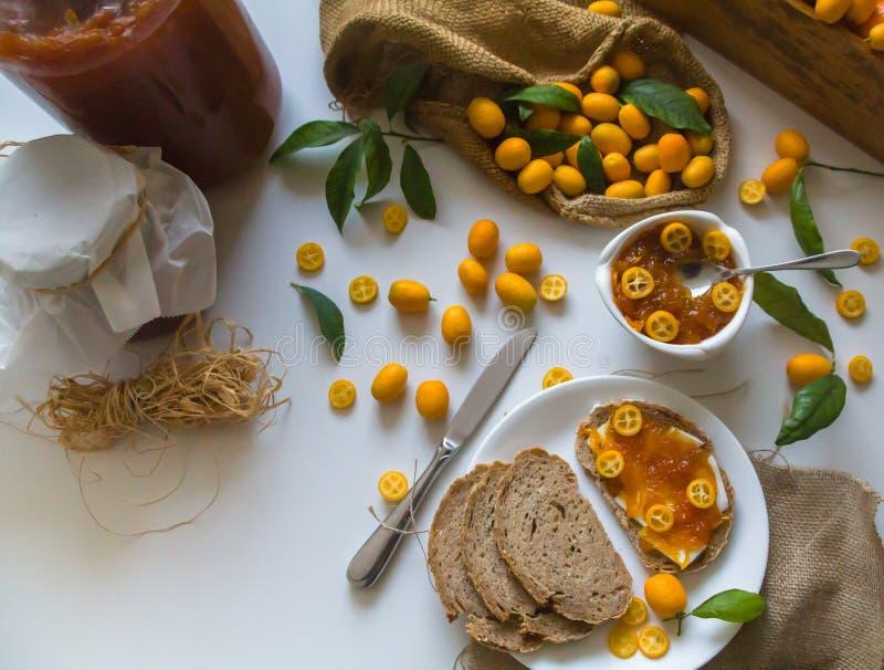 Sanduíches caseiros do pão de sourdough com doce e manteiga do Kumquat em uma placa branca foto de stock