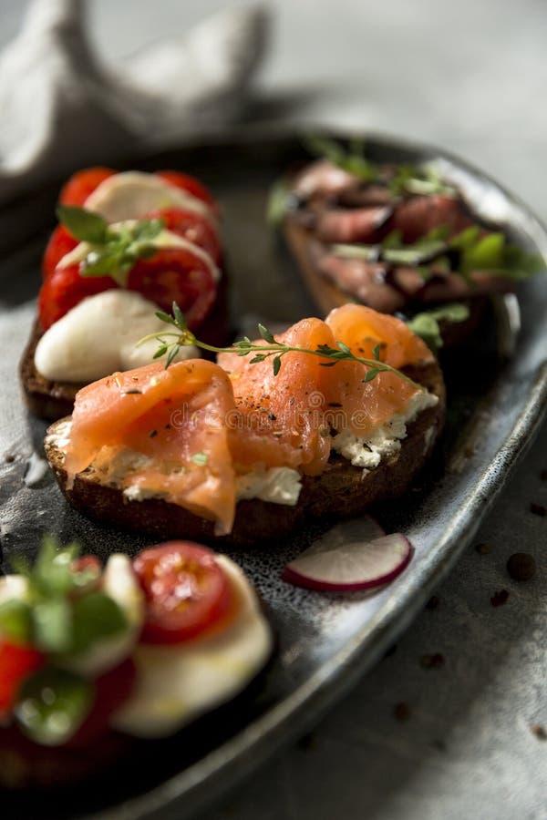 Sanduíches com carne assada e rúcula, salmões e cominhos, mussarela e tomates no pão de mistura foto de stock