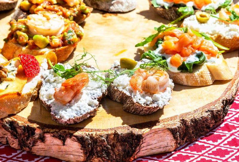 Sanduíches com enchimento diferente na placa de madeira fotografia de stock