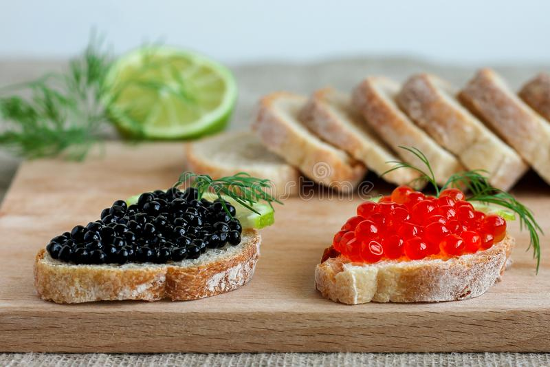 Sanduíches com o caviar vermelho e preto com cal fotos de stock royalty free