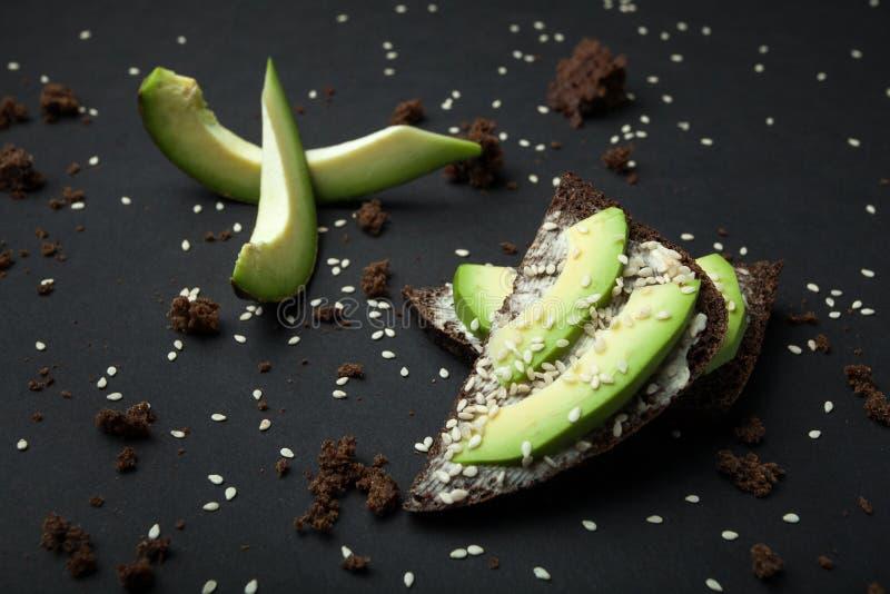 Sanduíches com pão de centeio, o abacate cortado fresco e as migalhas dispersadas em um fundo preto imagens de stock