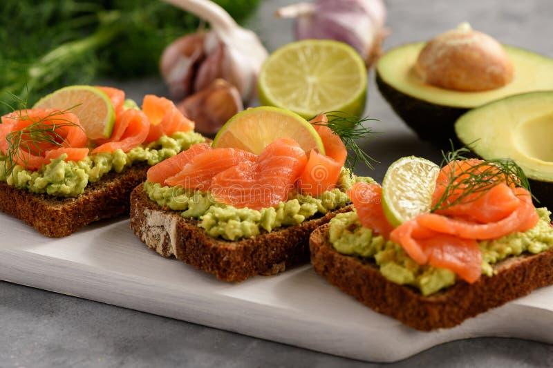 Sanduíches com propagação e salmão fumado do abacate fotografia de stock