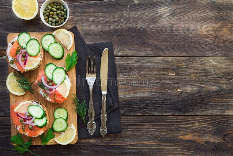 Sanduíches com salmão fumado, a cebola vermelha, as alcaparras, o pepino e o limão foto de stock royalty free