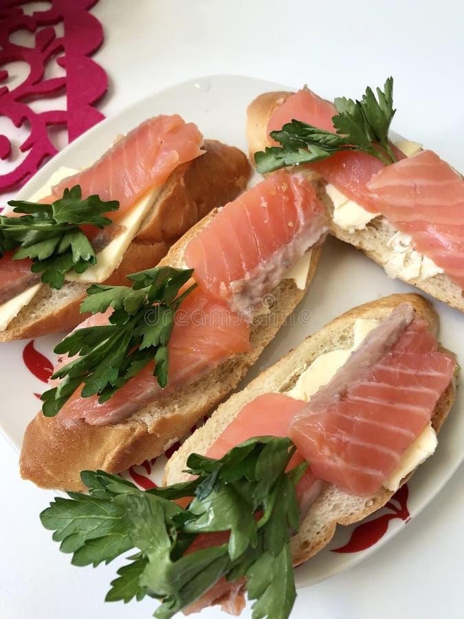 Sanduíches com salmões e verdes As partes de peixes são colocadas em um baguette do pão, lubrificado Decorado com salsa fresca fotos de stock royalty free