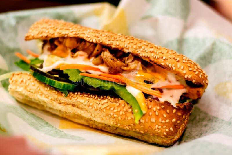 Sanduíches cozidos do sésamo com alface, tomates, carne, queijo e molhos fotos de stock royalty free