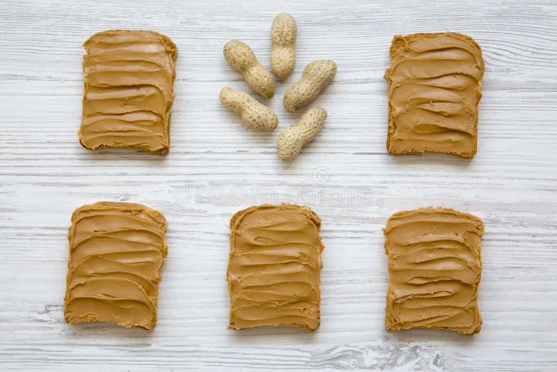 Sanduíches da manteiga de amendoim e amendoins unshelled em um fundo de madeira branco, fotografia de stock