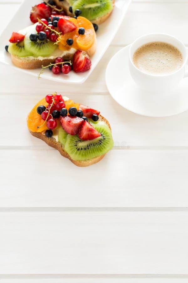 Sanduíches da sobremesa do café e do fruto com queijo da ricota, quivi, abricó, morango, mirtilo e o corinto vermelho imagens de stock royalty free