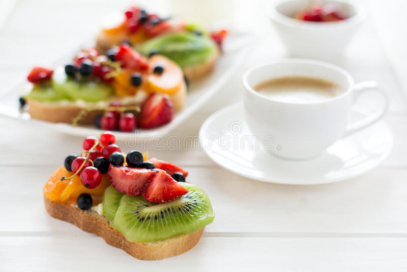 Sanduíches da sobremesa do café e do fruto com queijo da ricota, quivi, abricó, morango, mirtilo e o corinto vermelho imagem de stock royalty free