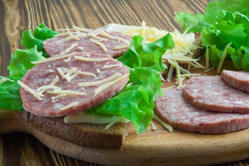 Sanduíches das salsichas da forma de sustento, da alface e do salame polvilhadas com o queijo raspado em uma placa de corte e em  fotos de stock