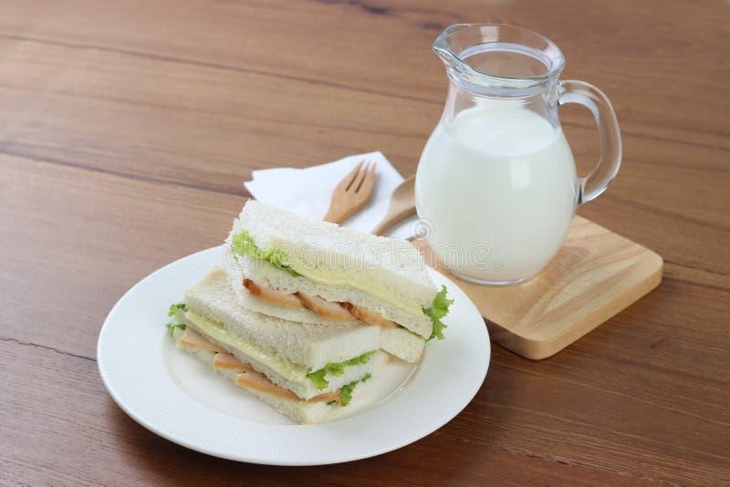 Sanduíches de galinha no prato branco com leite e forquilha e colher de madeira fotografia de stock