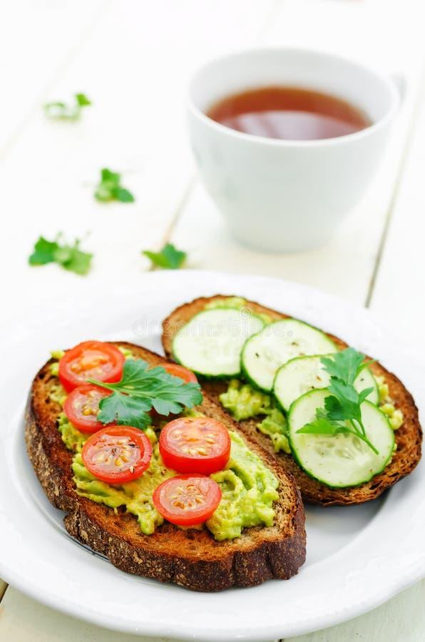 Sanduíches de Rye e abacate, ovos, tomates e pepinos triturados imagens de stock royalty free