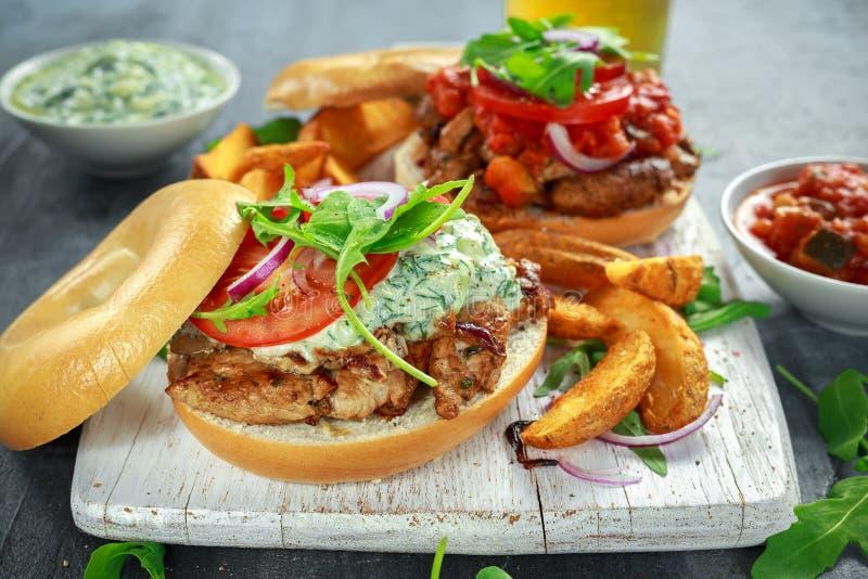 Sanduíches deliciosos da carne de porco do Bagel com vegetal e molho e fritadas de Tzatziki na placa branca foto de stock