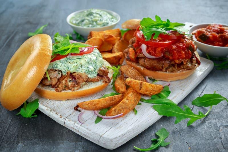 Sanduíches deliciosos da carne de porco do Bagel com vegetal e molho e fritadas de Tzatziki na placa branca fotografia de stock royalty free