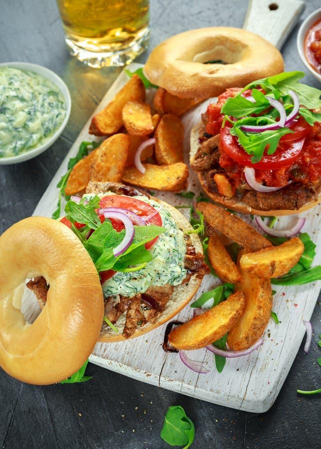 Sanduíches deliciosos da carne de porco do Bagel com vegetal e molho e fritadas de Tzatziki na placa branca imagens de stock