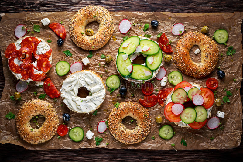 Sanduíches deliciosos do Bagel com queijo macio, chouriço e vegetais fotos de stock royalty free