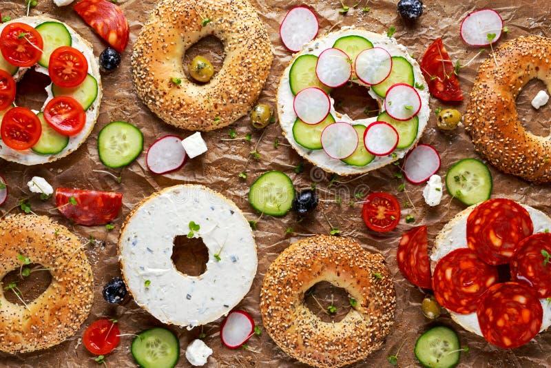 Sanduíches deliciosos do Bagel com queijo macio, chouriço e vegetais imagem de stock