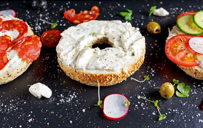 Sanduíches deliciosos do Bagel com queijo macio, chouriço e vegetais foto de stock